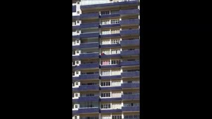 Homem se arrisca em sacada de janela para limpar janelas no Farol